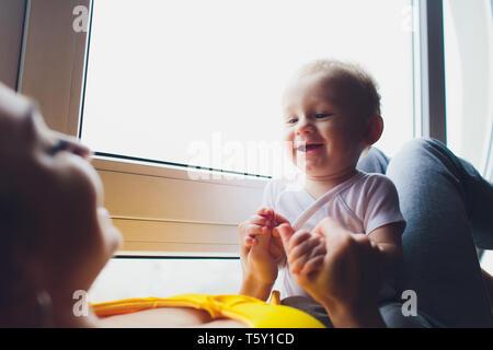 Liebevolle Mutter mit ihr spielen Babysitting auf ein Fenster. - Stockfoto