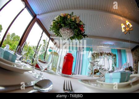 Tabelle Einrichtung mit handgefertigten Geschenkbox auf Platte, Blumenstrauß, Gläser, Gabeln, Löffel und Messer für Hochzeit. Guest Relation in Luxus deco - Stockfoto