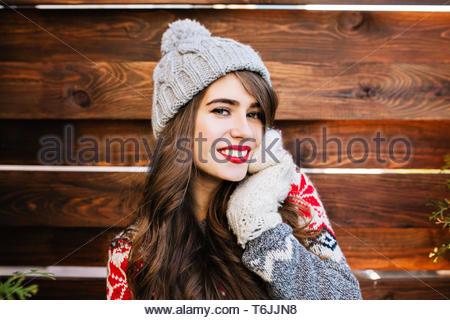 Portrait attraktives Mädchen mit langen Haaren und roten Lippen in Strickmütze auf Holz- Hintergrund. Sie ist das Berühren mit der Hand in die Handschuhe und lächelnd in die Kamera - Stockfoto