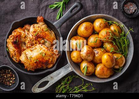 Gegrilltes Hähnchen und gebackene Kartoffeln in einer gusseisernen Pfanne, Ansicht von oben, dunklen Hintergrund. - Stockfoto