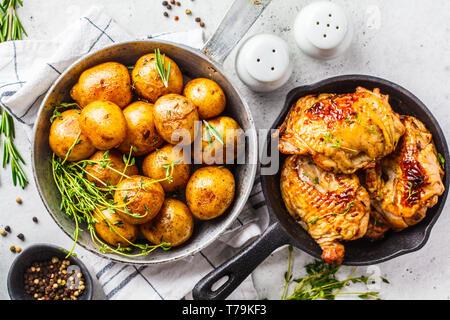 Gegrilltes Hähnchen und gebackene Kartoffeln in einer gusseisernen Pfanne. - Stockfoto