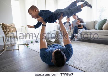 Verspielt Vater anheben Sohn Overhead im Wohnzimmer - Stockfoto