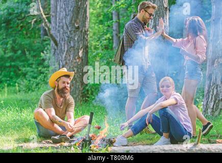 Melden Sie Sommer Picknick. Freunde treffen in der Nähe von Feuer zu hängen und gebratene Würstchen snacks Natur Hintergrund vorbereiten. Unternehmen Spaß beim braten Würstchen auf Sticks. Treffpunkt für die große Picknick. - Stockfoto