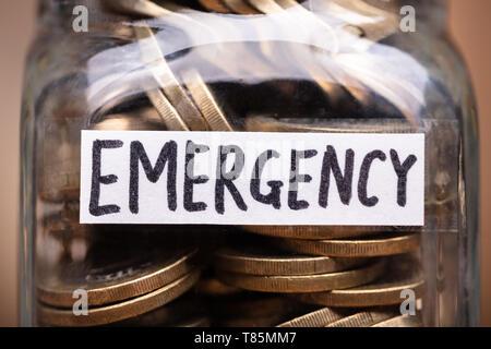 Münzen In den Jar mit Not Aufkleber über Holz- Schreibtisch - Stockfoto