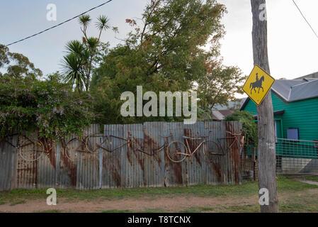 Ein Zeichen in einem Land Vorstadtstraße warnen Reiter vor und ein Wellblech Zaun mit dekorativen Fahrradteile kleben geblieben. - Stockfoto