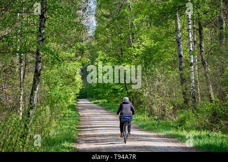 Nürnberg, Deutschland - 10. Mai 2019: eine Frau auf einem Fahrrad ist Reiten auf einer Schotterstraße durch das Schöne und Frische grüne Frühling Wald - Stockfoto