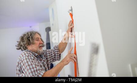 Elektriker installieren versenkte Verkabelung in einer Wand montage der Conduit in die Nut, Low Angle View in einem Haus Sanierungskonzept. - Stockfoto