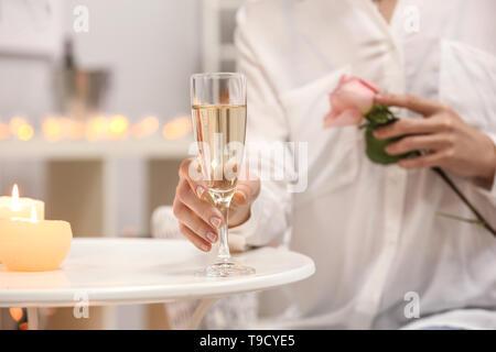 Junge Frau mit einem Glas Champagner und schöne Rose am weißen Tisch - Stockfoto
