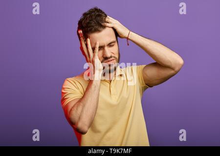 Stattliche unglücklichen Mann mit sehr starken Schmerzen und Holding Pillen, Tabletten. Kerl hat hohen Blutdruck. Bis schließen Foto.studio erschossen. Nutzlos, Medizin, Symptom - Stockfoto