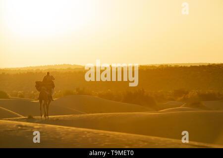 Atemberaubende Aussicht auf ein Mann auf einem Kamel reiten auf den Dünen der Wüste Thar in Rajasthan während des Sonnenuntergangs. Indien. Die Wüste Thar ist ein großer trockenen Region im - Stockfoto