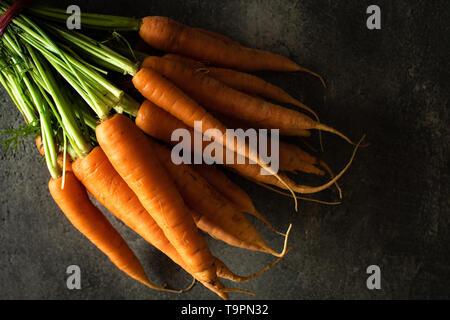 Nantes Karotten auf rustikalen dunklen Hintergrund. Frische organische Superfood Gesund Essen Konzept und Diabetes zu kontrollieren. - Stockfoto