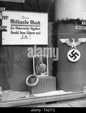 """In Österreich ist ein Referendum über den Anschluss Österreichs an das Deutsche Reich statt. In einem Wiener Schaufenster hängt ein Wahlplakat für die Volksabstimmung. Es lautet: """"Eine Milliarde Mark für Österreichs Straßen/Dank der Führer mit JA!"""". Unten ist ein Porträt von Adolf Hitler. - Stockfoto"""