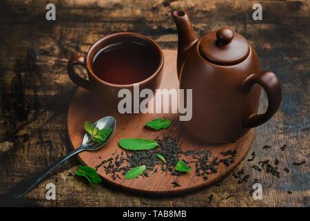 Pfefferminztee in braun Keramik Tasse und Kännchen auf einem warmen Holz- Hintergrund mit Kaffee brühen und Minzeblättchen. - Stockfoto