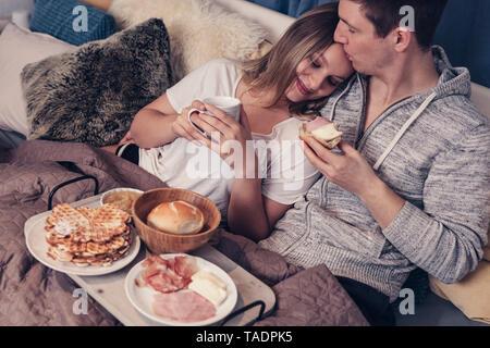 Junges Paar mit Frühstück im Bett - Stockfoto