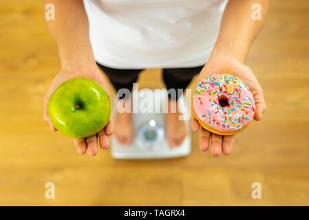 Nahaufnahme von Frau auf der Skala, in die Hände von Apple und Krapfen, die Wahl zwischen gesunden ungesunden essen Dessert während der Messung Körpergewicht in der Mutter - Stockfoto
