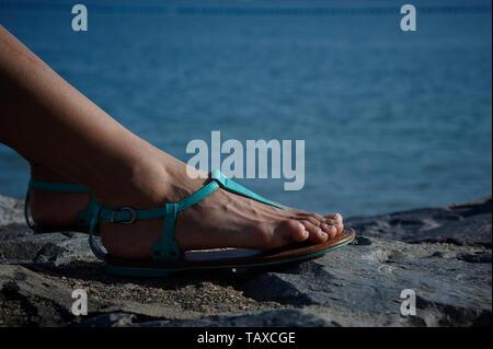 Füße der Frau Sandalen sitzen auf einem Felsen am Strand im Sommer Sonnenschein - Stockfoto