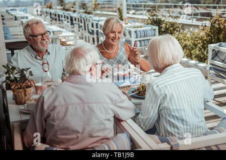 Fröhliche bärtiger Mann im Gespräch mit seinen Freunden - Stockfoto