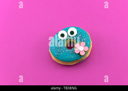 Lustig blau glasiert Donut auf rosa Hintergrund. Pastell - Stockfoto