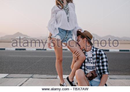 Junger Mann in Trendy Shirt und vintage Hut sitzen auf der Straße, witzigen küssen Bein seiner Freundin. Schlanke Mädchen in Denim Shorts um Narren mit ihrem Freund, verbringt Zeit im Freien in der Nähe von Highway - Stockfoto