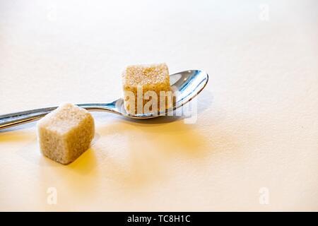 Rohrzucker Würfel und ein Löffel auf einen Tisch. - Stockfoto