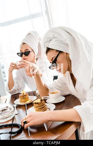 Stilvolle Frauen in Bademänteln, Sonnenbrillen und Schmuck mit Handtüchern auf Staats- und Pfannkuchen essen für Frühstück - Stockfoto
