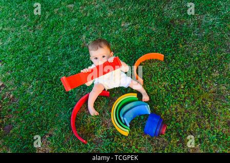 Baby spielt mit einem bunten Regenbogen aus Holz auf dem Gras, geistige und seelische Entwicklung. - Stockfoto