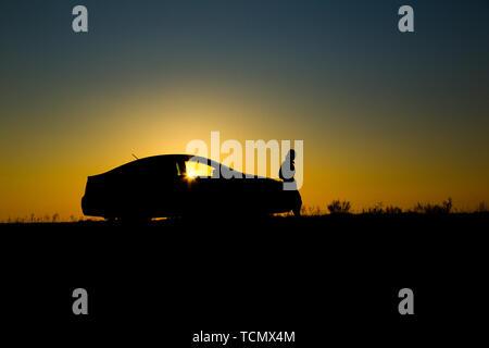 Silhouette der Limousine mit Mädchen vor dem Hintergrund der schönen Sonnenuntergang - Stockfoto