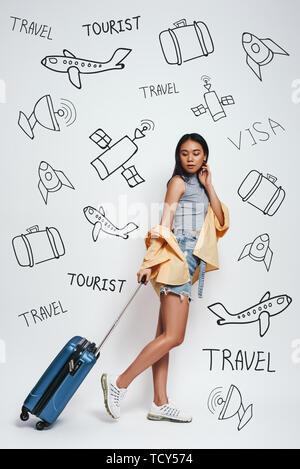 Bereit für ein Abenteuer! Die ganze Länge der lächelnde schöne asiatische Frau carrieng Ihr Gepäck gegen grauen Hintergrund stehend mit Gekritzel auf der Sie - Stockfoto
