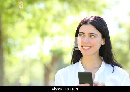 Vorderansicht Portrait eines glücklichen erwachsenen Frau mit Smart Phone und denken an der Seite, die in einem Park - Stockfoto