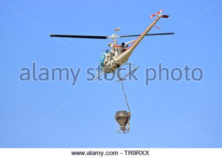Schließen, Vollständiges Profil anzeigen von einem Hubschrauber in der Luft und ist mit einem Wassereimer, die für die Bekämpfung von Waldbränden eingesetzt wird. - Stockfoto