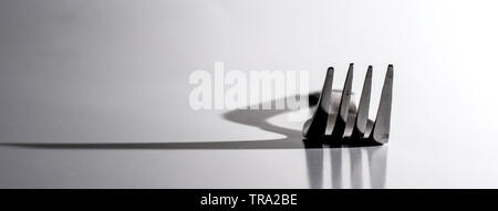 Abendessen Gabel wirft große Schatten auf weißem Hintergrund. Konzept von Schatten und Licht. - Stockfoto