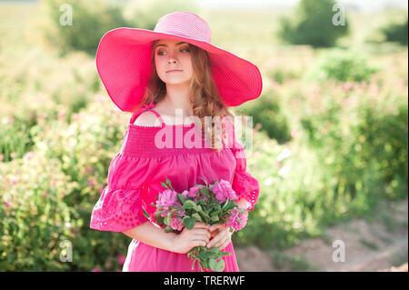 Smiling teenage Mädchen 14-16 Jahre alten tragen rosa kleid und hut Holding Rosen im Freien. Weg schauen. Sommer. - Stockfoto