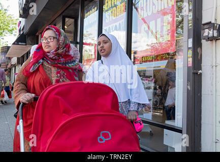 Zwei muslimische Frauen in hijabs, wahrscheinlich Schwestern, gehen Sie die 74th St. in Jackson Höhen treibt ein rotes Baby Stroller. Queens, NYC. - Stockfoto