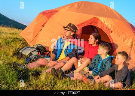 Familie genießt die Abendsonne vor einem Zelt - Stockfoto