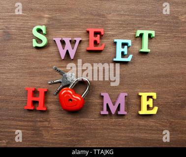 Dekorativer Buchstaben Wörter bilden SWEET HOME mit Schloss und Schlüssel auf hölzernen Hintergrund - Stockfoto