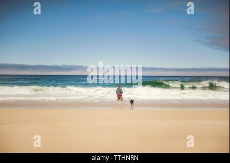 Ansicht der Rückseite des Mann mit Hund am Ufer gegen Sky - Stockfoto