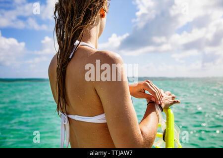Woman Holding beim Stehen in der Meer gegen bewölkter Himmel Schnorcheln - Stockfoto