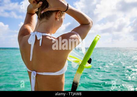 Frau mit Schnorchel einstellen Haar beim Stehen in der Meer - Stockfoto