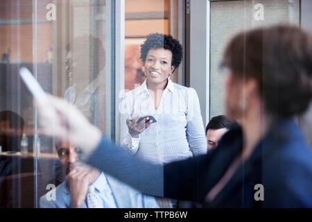 Happy Geschäftsfrau Holding smart phone und Kollegen eine Präsentation halten im Amt suchen - Stockfoto