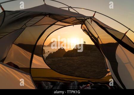 Fernsicht auf Paar steht auf Rock Formation durch Zelt gesehen - Stockfoto