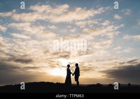 Silhouette Paar Hände halten beim Stehen auf Feld gegen bewölkter Himmel bei Sonnenuntergang - Stockfoto