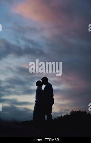 Silhouette paar Küssen beim Stehen auf Feld gegen bewölkter Himmel bei Sonnenuntergang - Stockfoto