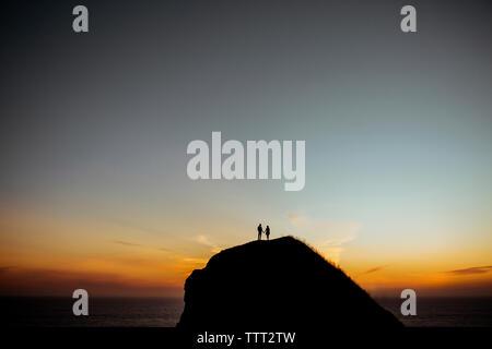 Fernsicht auf Paar stehend auf silhouette Klippe gegen Himmel von Meer bei Sonnenuntergang - Stockfoto