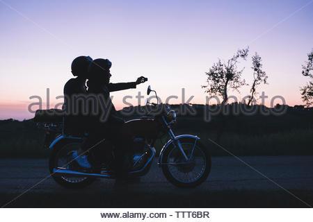 Silhouette junge Paar unter selfie während auf Motorrad während der Dämmerung sitzen - Stockfoto