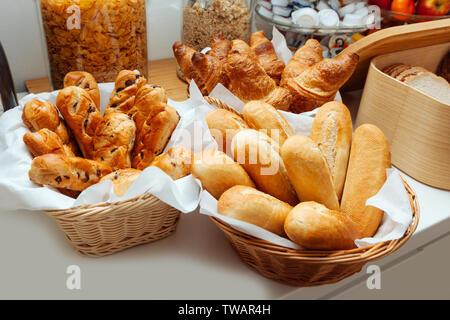 Bäcker backen zog frische Croissants und Brötchen aus dem Ofen. Frauen Hände in weißen Handschuhen halten Sie einen Korb mit heißem Gebäck - Stockfoto