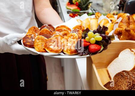 Baker zog frische Backen pancaks und Brötchen aus dem Ofen. Frauen Hände in weißen Handschuhen halten Sie eine Platte mit heißem Gebäck. - Stockfoto