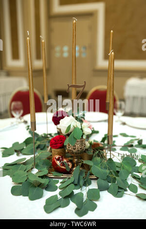 Festlich runde Tafel im Restaurant eingerichtet. Frische Blumen sind goldene Kerzen und roten Stühlen. teuer reichen. - Stockfoto