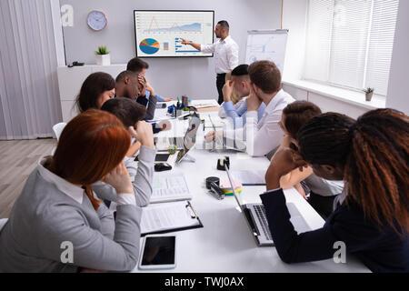 Gruppe von Führungskräften müde vom langen Sitzung im Amt - Stockfoto