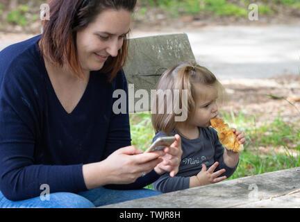 Mutter und ihrer Tochter im Park sitzen. Mutter sms eine Nachricht auf dem Smartphone, Mädchen mit Croissant. Natur Szene - Stockfoto