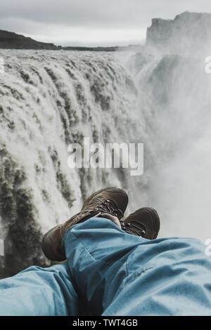 Füße in Trekking Schuhe mit Blick auf den Wasserfall Dettifoss in Island. Atemberaubend und dramatischen Blick. Wandern auf Island Wahrzeichen. - Stockfoto